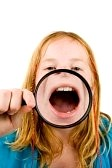 5912890-little-girl-is-showing-her-mouth-through-a-magnifying-glass-over-white